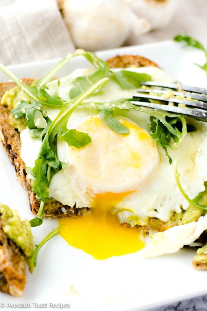 Avocado toast with arugula and over easy egg